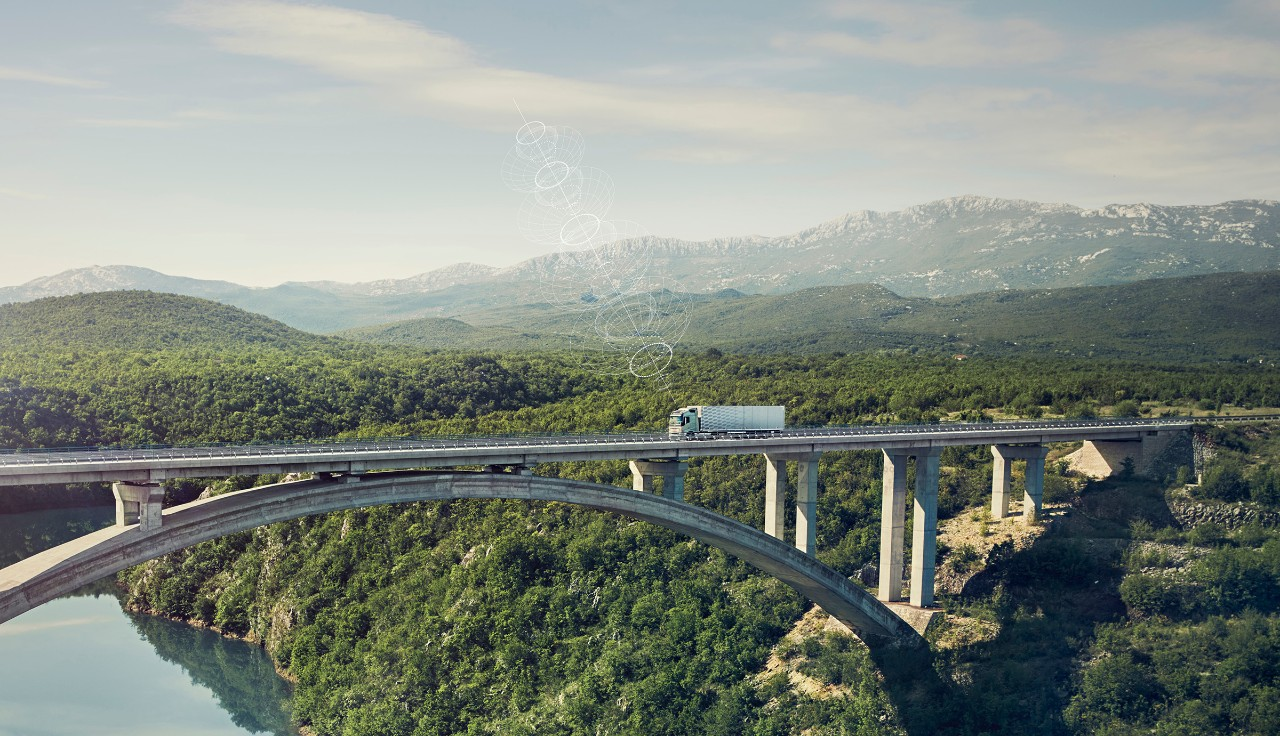 Un camión Volvo conectado cruza un puente en una ubicación remota