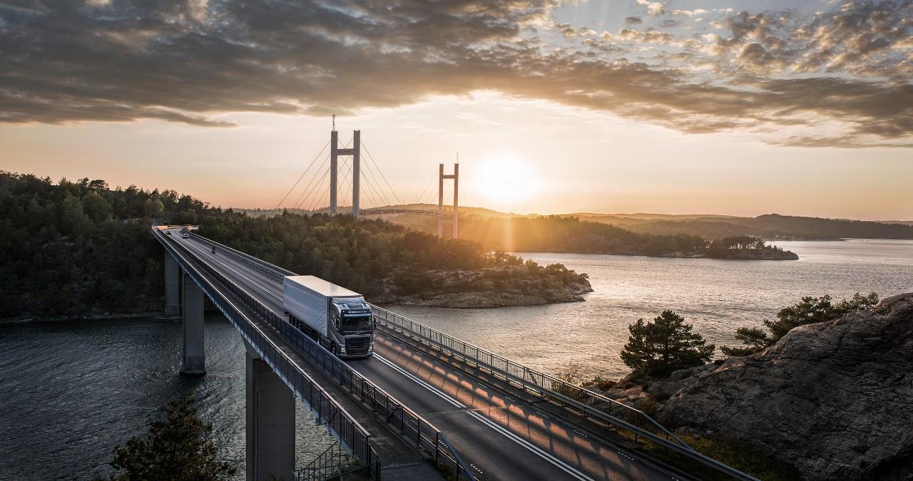 Un camión Volvo pasa por un puente sobre el agua mientras el sol se pone detrás de él